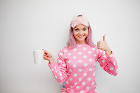 Good Morning. Smiling young woman shows thumb up and drinks coffee. Girl in pink pajamas and sleep mask on white background Stock Photo