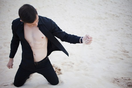 Loss, concept. A young man kneeling in the desert. Sand through fingers