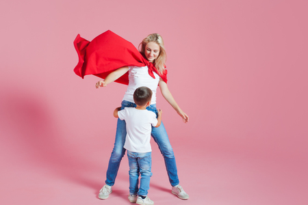 Mom is a superhero. Fun family, a young blond woman in a red Cape and her son, pink background Stock Photo