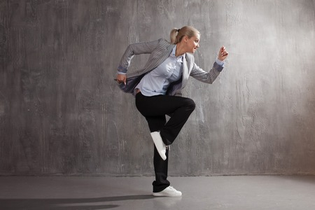 Young woman in business suit and sneakers. runner's pose, ready to run a long distance, concept business or startup Foto de archivo
