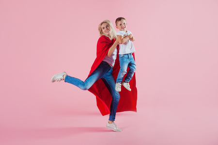 Mom is a superhero. Fun family, a young blond woman in a red Cape and her son jumps and takes off, pink background