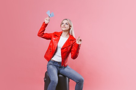 Happy young woman with travel suitcase launches paper airplane. Blonde tourist girl on pink background, concept, travel or vacation