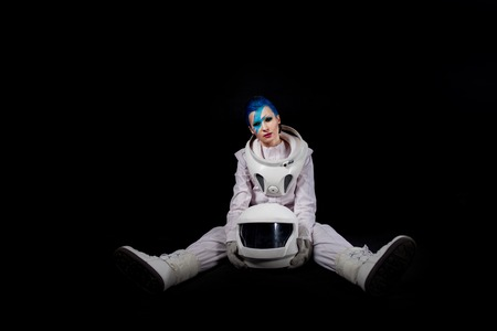 Astronaut on a black background, a young woman with face art in the space suit. sits
