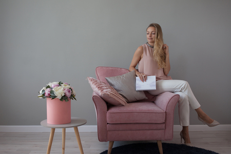 Young friendly woman sitting in a chair with a notebook in her hands. Stylish interior design, a bouquet of flowers. A nice companion. Light gray background, copy space Stockfoto