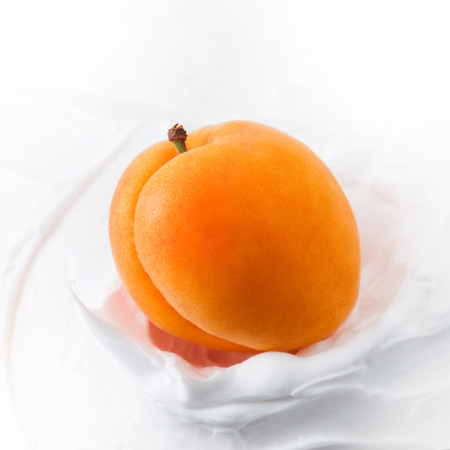 Yogurt with Fresh delicious apricot. piece of fruit in juicy apricot in yogurt, milk or cheese mass, close up