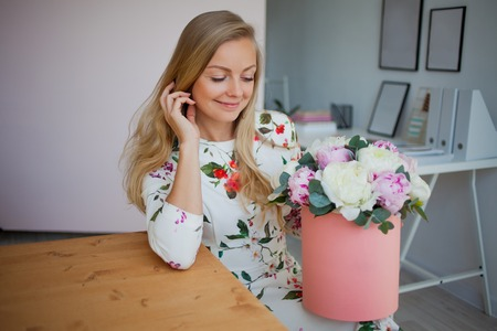 Happy blonde woman in a modern office with flowers in a hat box. Bouquet of peonies. Flower delivery to the workplace Stockfoto