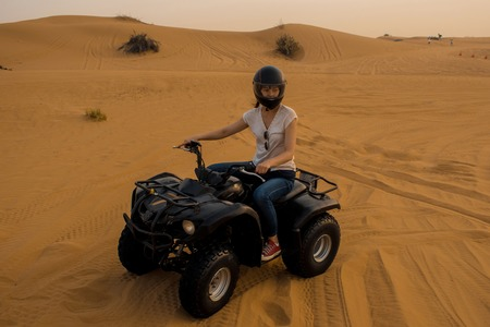 desert Quad Biking. Young girl in a helmet driving a Quad bike