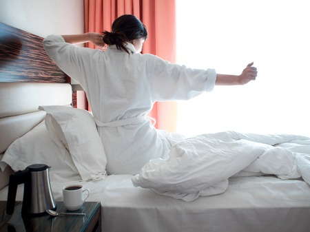 young woman in a white Terry robe woke up this morning. in the hotel