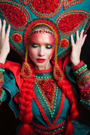 Girl in a headdress. Portrait of a beautiful young woman in a stylized Russian suit