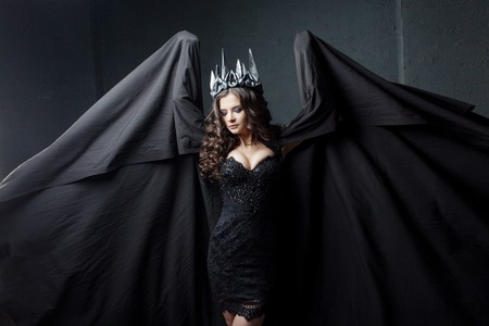 Portrait of a Gothic Princess. Beautiful young brunette woman in metal crown and black cloak. Mystical image Stock Photo