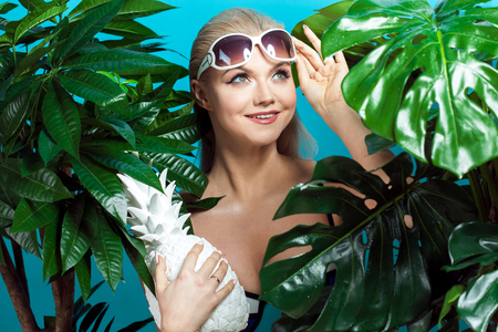 Young woman in blue bikini on blue background. Funny girl with sunglasses and white pineapple Imagens