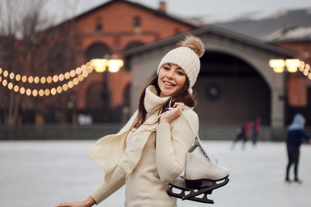 Charming young woman in the Park near the ice rink. Happy young woman in knitted sweater and hat is going skating