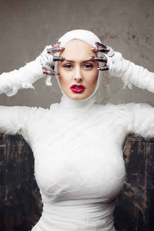 Glamorous mummy. Portrait of a young beautiful woman in bandages all over her body. Halloween or plastic surgery concept