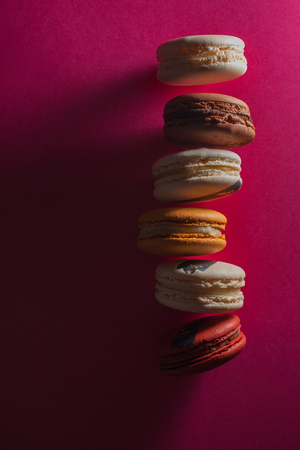 Elegant French desserts. Set of colorful macaron decorated by confectionery colours and toppings. low key Style