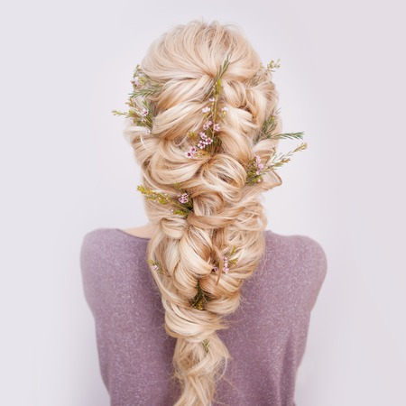 Back view of an elegant trendy hairstyle, interlacing curls and decorating with flower petals. Beautiful and well-groomed blonde hair Imagens