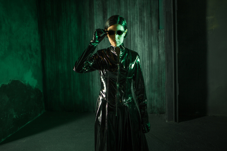 Girl hacker in the digital world. Young woman in matrix style suit. Black leather and sunglasses on black background