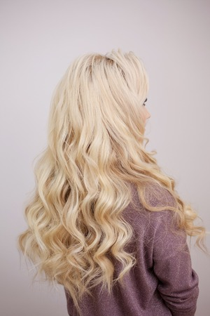Back view of blonde with long luxurious curls. Beautiful and healthy hair, care and coloring