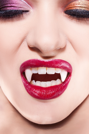 Vampiro sexy. Labios de mujer con lápiz labial rojo. Sonrisa de vampiro