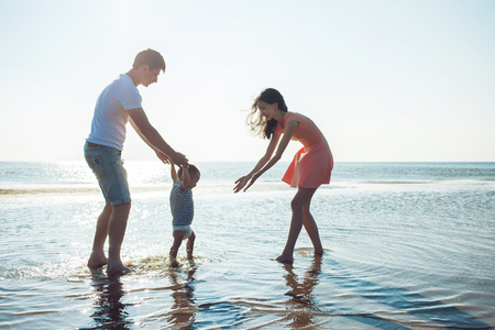 Mom and dad teach baby to walk. Young happy family walking on the beach