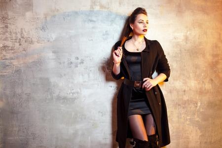 Stylish and daring brunette in black, portrait on grey background 免版税图像