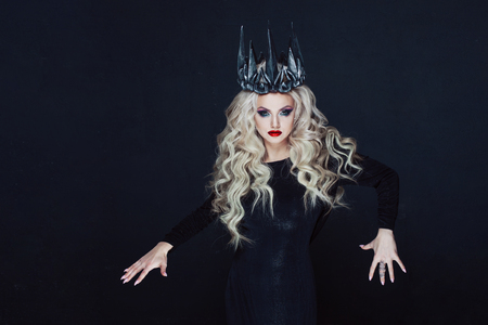 Portrait of a Gothic Princess. Beautiful young blonde woman in metal crown and black cloak. Mystical image Фото со стока