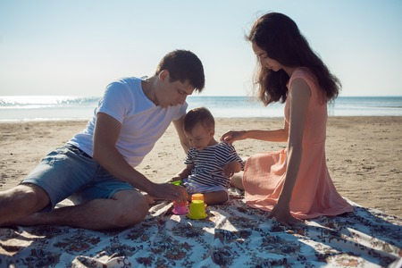 Cheerful multi ethnic family have a rest on a sea shore. Young family, man woman and little son enjoy picnic, summer outdoor, good weather