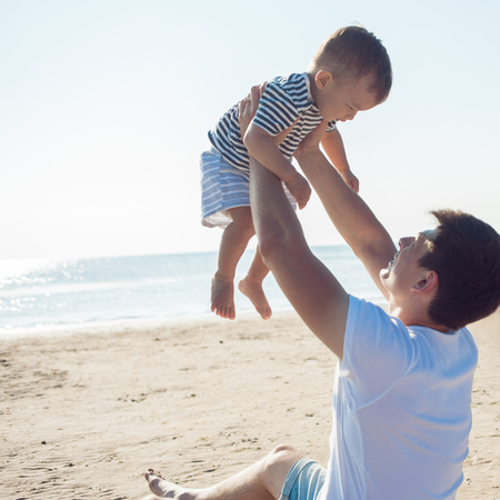 Cheerful multi ethnic family have a rest on a sea shore. Young father raises his son up