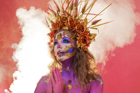 Bright Halloween image, Mexican style with sugar skulls on the face. Young beautiful woman bright daring image in a crown of roses. Pink background