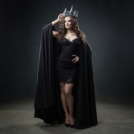 The dark Queen. Attractive and sexy young woman in long black cloak and crown. Got the title, dark background