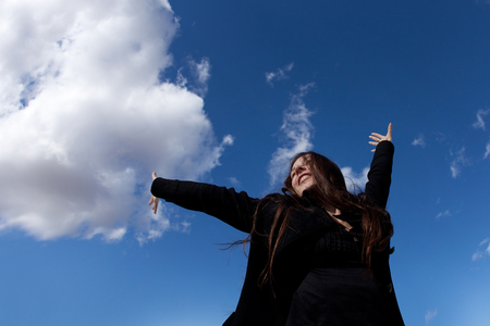 Happy young brunette in black clothes enjoys freedom on blue sky background