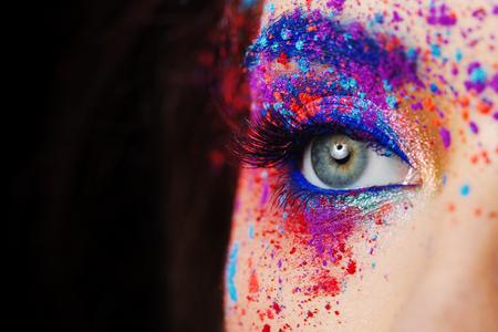 explosión de color, sombras multicolores esparcidas por los párpados. Ojos ahumados coloreados y cejas azules. Retrato de moda de cerca