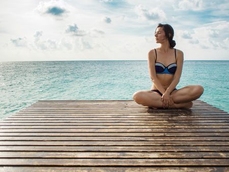 Young woman sitting in lotus pose on a background of beautiful sky and sea. Relax on a tropical island, maldivian resort