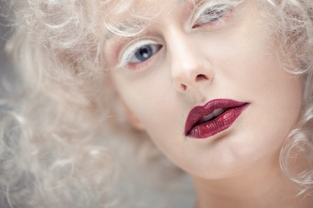 Young attractive woman with platinum blonde and purple lipstick. Fashion portrait in white style