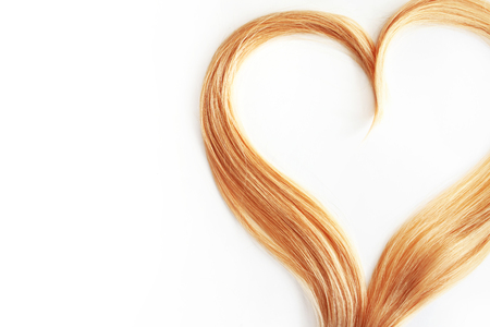strand of blond hair isolated on white. Curls of hair in the shape of a heart, health and hair care concept Stok Fotoğraf
