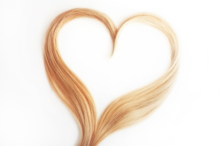 strand of blond hair isolated on white. Curls of hair in the shape of a heart, health and hair care concept Imagens