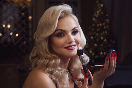 Beautiful young blonde makes a bright holiday makeup. Glamorous make-up. An attractive young woman uses powder. Festive new year background