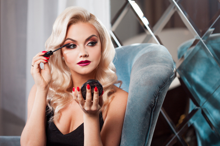 Beautiful young blonde makes a bright holiday makeup. Glamorous make-up. An attractive young woman paints the eyelashes