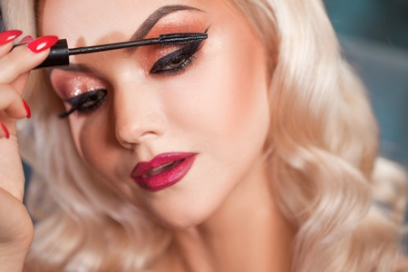 Beautiful young blonde makes a bright holiday makeup. Glamorous make-up. An attractive young woman uses mascara
