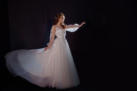 Young beautiful woman in wedding dress with wide light skirt. Dark background, fantasy style. stretch a hand somewhere