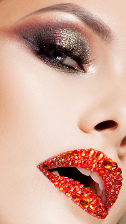 Bright eye makeup and red lips in rhinestones. Smokey eyes, colored eyeshadow. Close up Stock Photo