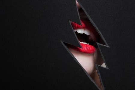 Beautiful woman with bright red lips. Cutout in paper in the form of a lightning. Free space