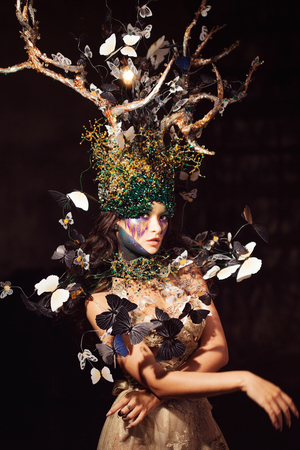 natural nymph with horns like branches of a tree and butterflies circling around. Fantasy style costume, young beautiful girl in the image of flora