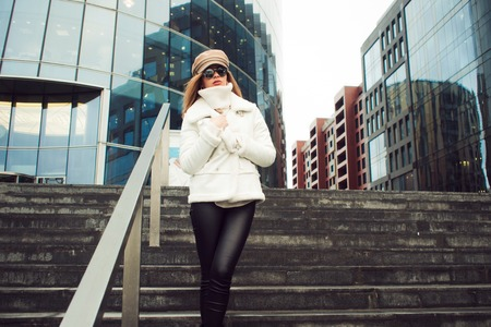 Stylish and elegant young woman on the background of the business center. Beautiful girl in white jacket and cap, walk