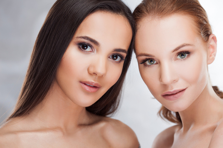 Bellezza naturale. Due ragazze diverse, ritratto di bellezza. Due giovani belle donne di diversa carnagione, tipo orientale e occidentale