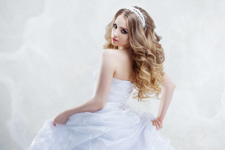 Charming young bride with luxury hairstyle. Beautiful woman in wedding dress. Hairstyle with fluffy curls. Portrait on light background