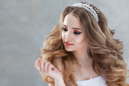 Beautiful young bride with lush curls, looking at something on the left. Wedding fashion and accessories