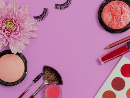 Set for professional makeup, different brushes for applying powder and eyeshadow. Cosmetics and Foundation, concept on purple background