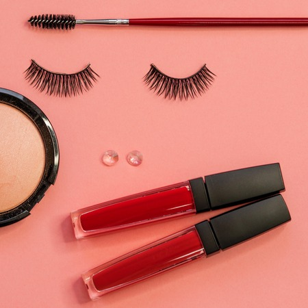 Eyelashes, powder eyebrow brush and lipstick as a beautiful face, concept on pink background. Makeup tools, eyelashes and eyebrow care