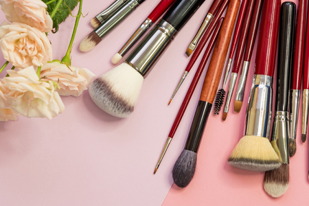 Set of different brushes for professional makeup, a multifunctional set of professional makeup artist. Brushes for application, shading. For eyes and Foundation, still life on a pink background Foto de archivo