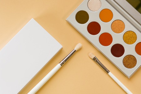 Set for eye makeup, eyeshadow in a palette and brush for a good application. still life on yellow background